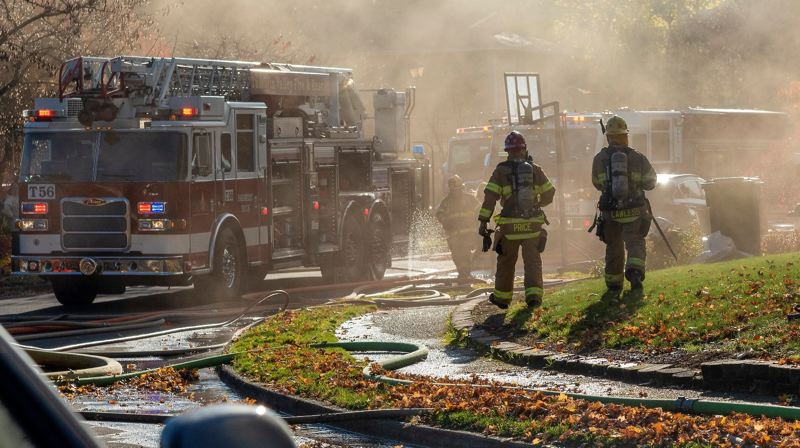 COURTESY PHOTO: TUALATIN VALLEY FIRE & RESCUE - Firefighters walk through smoke at the scene of a complex residential fire in Tualatin's Martinazzi Woods neighborhood on Friday morning, Nov. 1.
