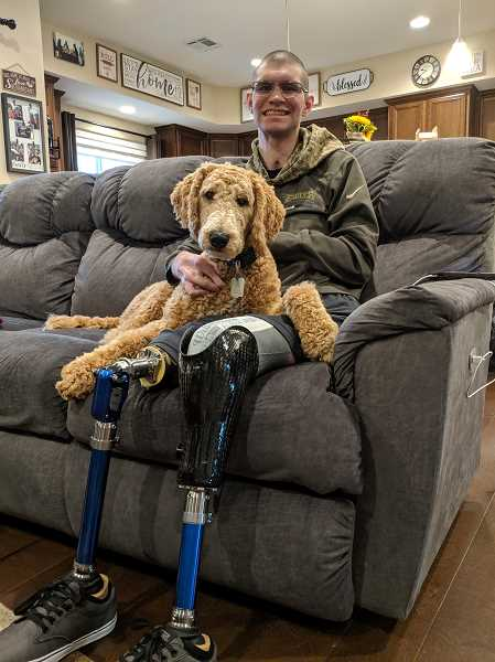 COURTESY PHOTO - Veteran Alex Hussey sits with six month old trained service dog Trooper. Hussey lost both of his legs, left hand, and sustained a traumatic injury while serving in Afghanistan.
