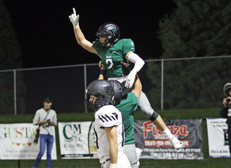 PMG PHOTO: DAN BROOD - Tigard High School senior Tyler Penn (2) celebrates with junior Edward Beglaryan after catching a 29-yard touchdown pass during the Tigers' 23-21 win over rival Tualatin.