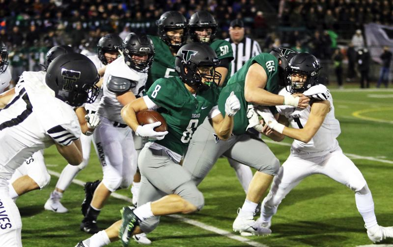 PMG PHOTO: DAN BROOD - Tigard High School senior Josh Burns (8) is about to break into the clear behind the block of senior Bryce Goetz on his way to scoring on a 73-yard touchdown run in Friday's game.