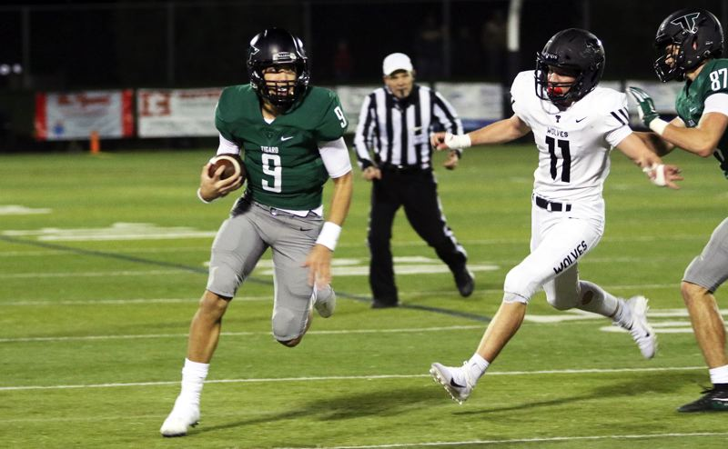 PMG PHOTO: DAN BROOD - Tigard High School junior quarterback Drew Carter (left), with Tualatin senior Jake Reser in pursuit, scrambles for yardage during the Tigers' 23-21 win on Friday.