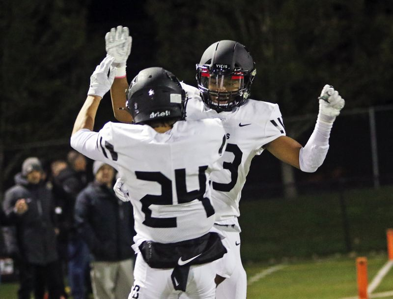 PMG PHOTO: DAN BROOD - Tualatin's Ethan Mendoza (24) and Malik Ross celebrate following Ross' 37-yard touchdown pass play during Friday's Three Rivers League game at Tigard.