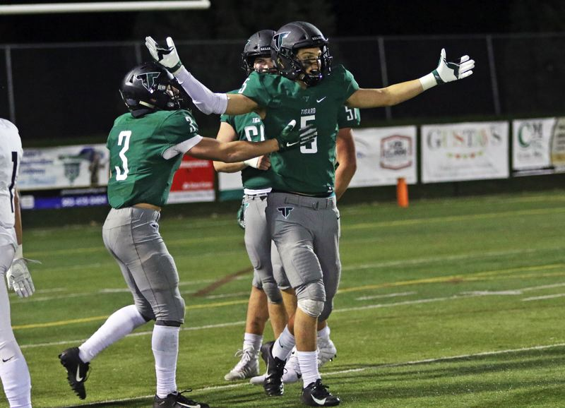 PMG PHOTO: DAN BROOD - Tigard High School senior linebacker Andrew Carter celebrates after making a tackle for a loss in the Tigers' 23-21 win over rival Tualatin on Friday.