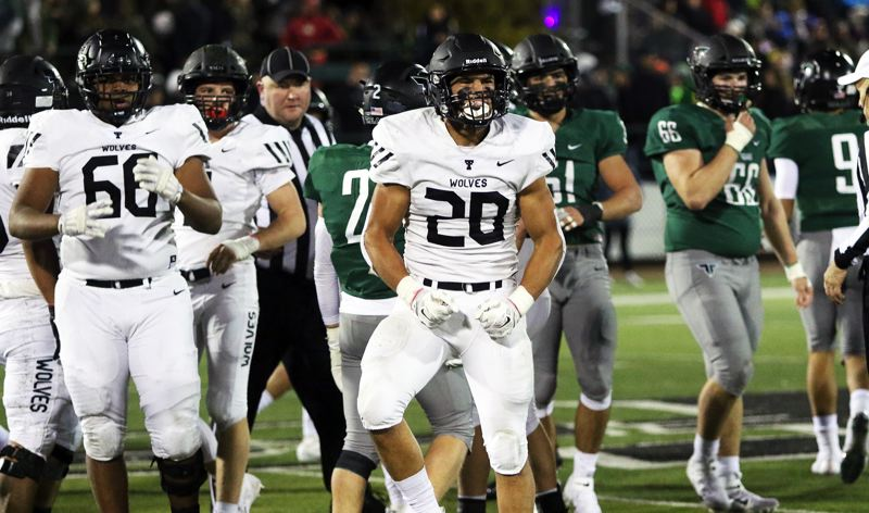 PMG PHOTO: DAN BROOD - Tualatin High School senior linebacker John Miller (20) celebrates after making a fourth-down tackle during the Wolves' game at Tigard on Friday.
