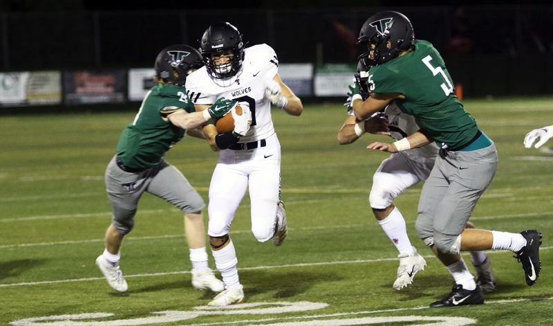 PMG PHOTO: DAN BROOD - Tualatin High School senior Luke Marion looks to get past some Tigard defenders during Friday's Three Rivers League showdown.