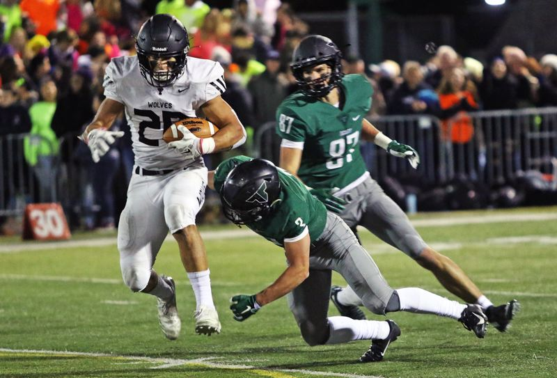 PMG PHOTO: DAN BROOD - Tualatin High School senior tight end John Miller (left) looks to pick up yardage after making a leaping catch during Friday's game at Tigard.