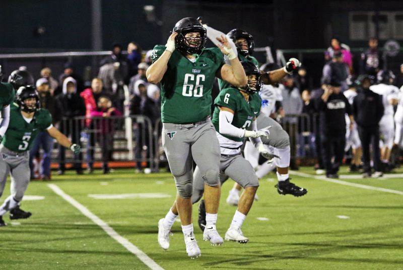 PMG PHOTO: DAN BROOD - Tigard High School senior lineman Bryce Goetz (66) and the rest of the Tigers start to celebrate following their 23-21 win over Tualatin.