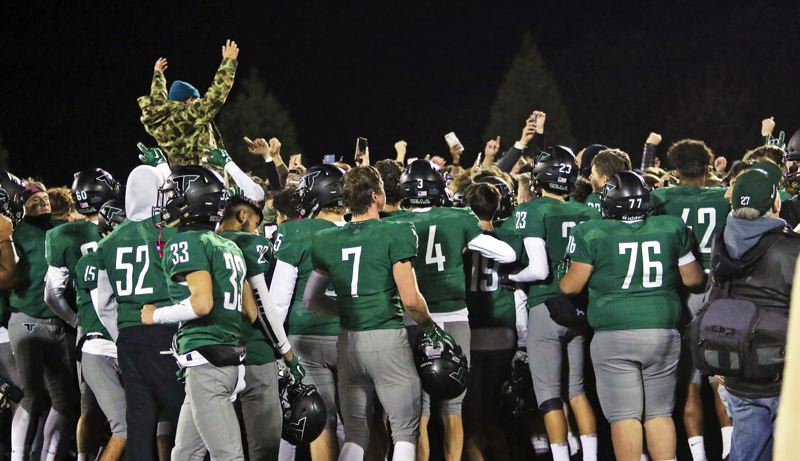 PMG PHOTO: DAN BROOD - Tigard High School player and fans celebrate following the Tigers' 23-21 win over Tualatin in Friday's Three Rivers League showdown.