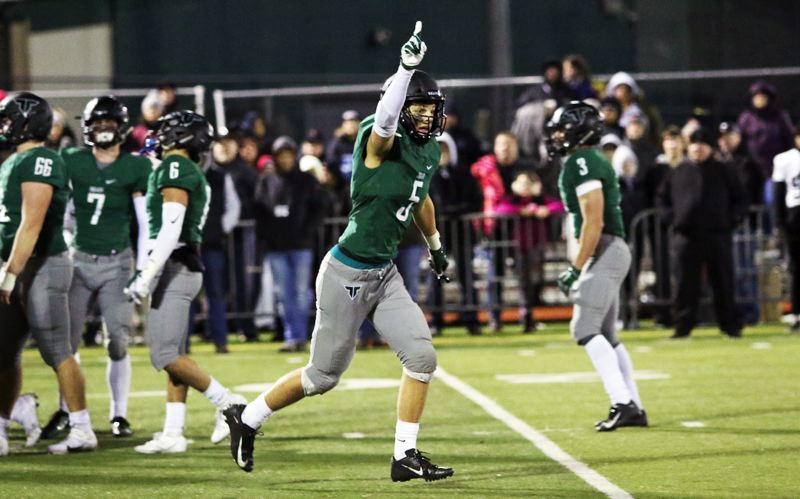 PMG PHOTO: DAN BROOD - Tigard's Andrew Carter runs off the field signalling that his top-ranked Tigers had just completed their unbeaten regular season by beating Tualatin 23-21 at Tigard High School on Friday, Nov. 1.