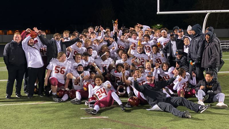 PMG PHOTO: JIM BESEDA - Central Catholic coach Steve Pyne (seated, front right) celebrates after the Rams defeated Clackamas 48-7 in Friday's Mt. Hood Conference championship game at Clackamas High School.