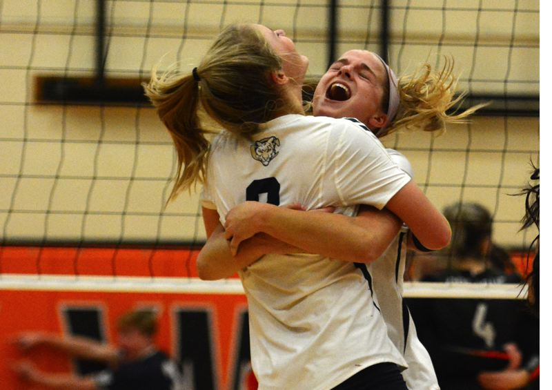 PMG PHOTO: DEREK WILEY - Ruby Kayser and Daley McClellan hug after Canby wins 3-2 at Sprague.