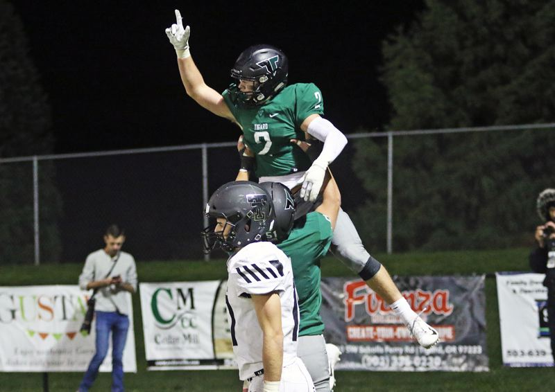 PMG PHOTO: DAN BROOD - Tigard's Tyler Penn gets hoisted into the air after scoring what turned out to be the winning touchdown in his team's 23-21 win over Tualatin at Tigard High School on Friday, Nov. 1.