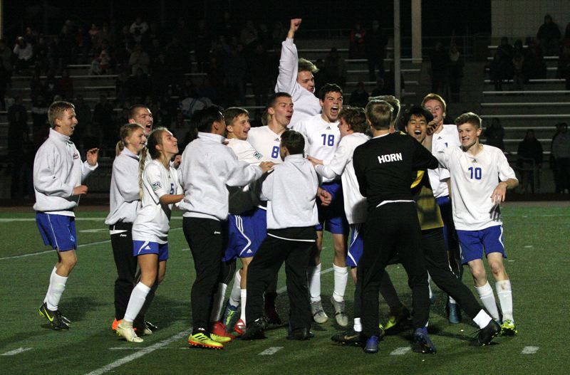 PMG PHOTO: JIM BESEDA - North Clackamas Christian players surround senior co-captain Braden Young (8) after his shot in the fifth round of the penalty-kick shootout lifted the Saints to a 2-1 win over Crosshill Christian.