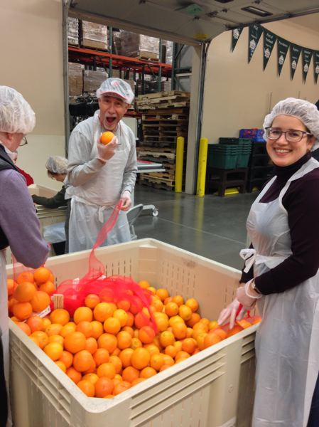 COURTESY: SAMUELS YOELIN KANTOR - Samuels Yoelin Kantor lawyer Emily Clark Cuellar and now-retired attorney Alan Spinrad lend a hand at a Portland-area food bank.