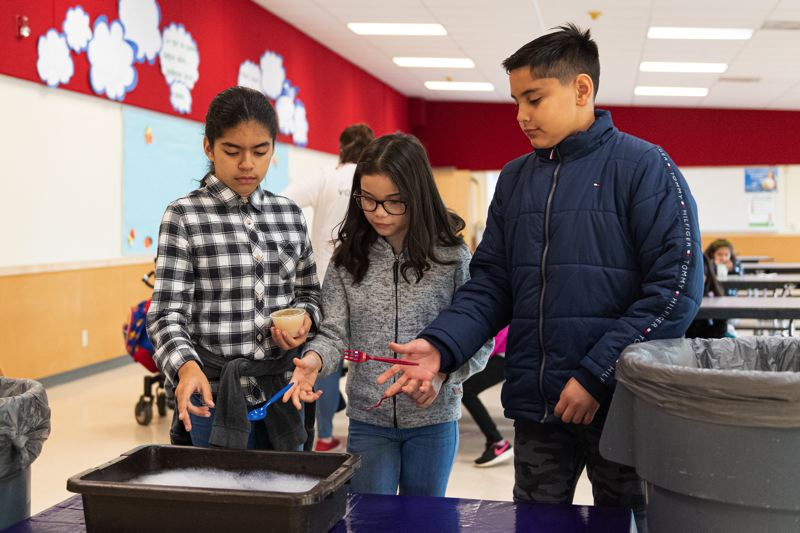PMG PHOTO: CHRISTOPHER OERTELL - Echo Shaw Elementary 5th graders Jocelyn Chavez, Sofia Ramos and Danny Cervantes, left to right, toss forks and spoons in a bin so they can be washed and reused. The students recently advocated for the school to do away with disposable utensils in the cafeteria.