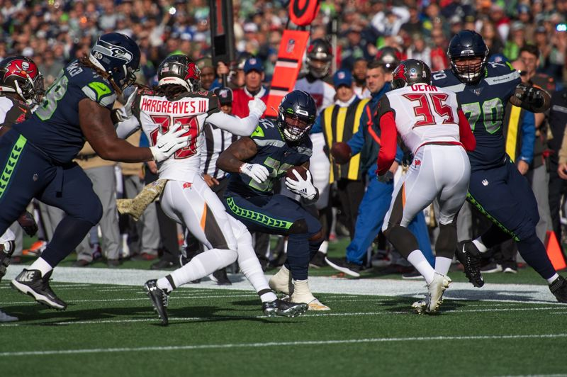 MICHAEL WORKMAN PHOTO - Seahawks running back Chris Carson looks for an opening.