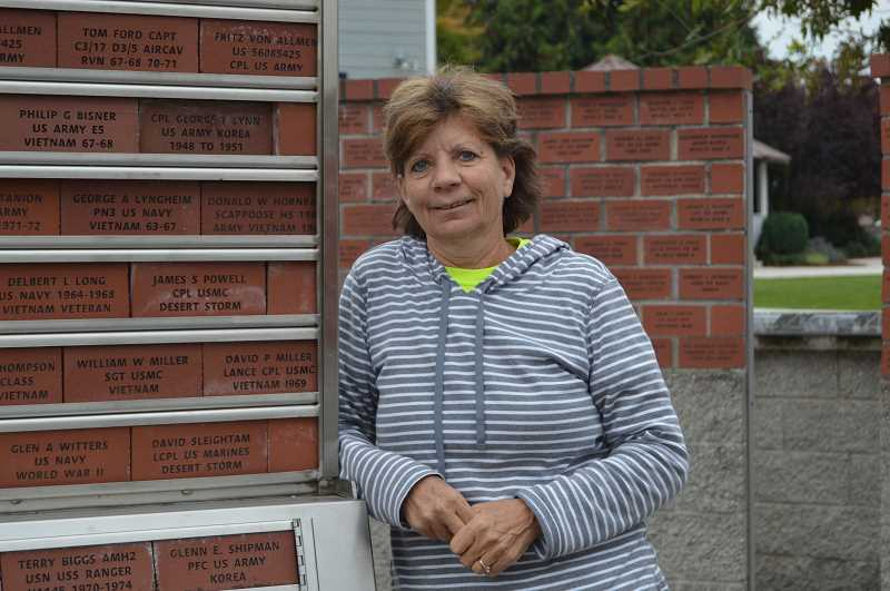 PMG PHOTO: NICOLE THILL-PACHECO - Carolyn Jenkins, 58, of Warren, pauses for a photo near the Scappoose Veterans Memorial in Heritage Park. While Jenkins does not have an honorary brick in the memorial, several of her family members do.