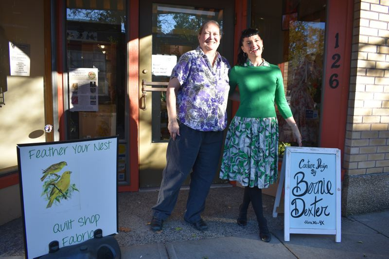 PMG PHOTO: SHANNON O. WELLS - Kris Howatt, owner of Feather Your Nest Quilt Store, and Bernie Dexter of her self-named dress shop smile outside their Main Avenue businesses, which recently swapped storefront spaces with each other.