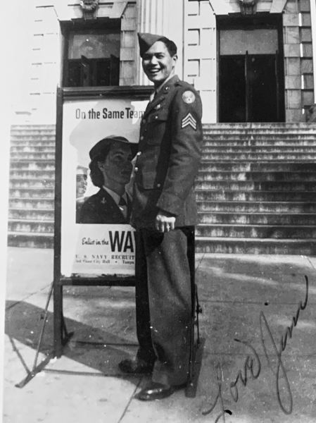 COURTESY PHOTO - In this 1944 photograph, James Hong stands next to a poster encouraging enlistment in the U.S. war effort.