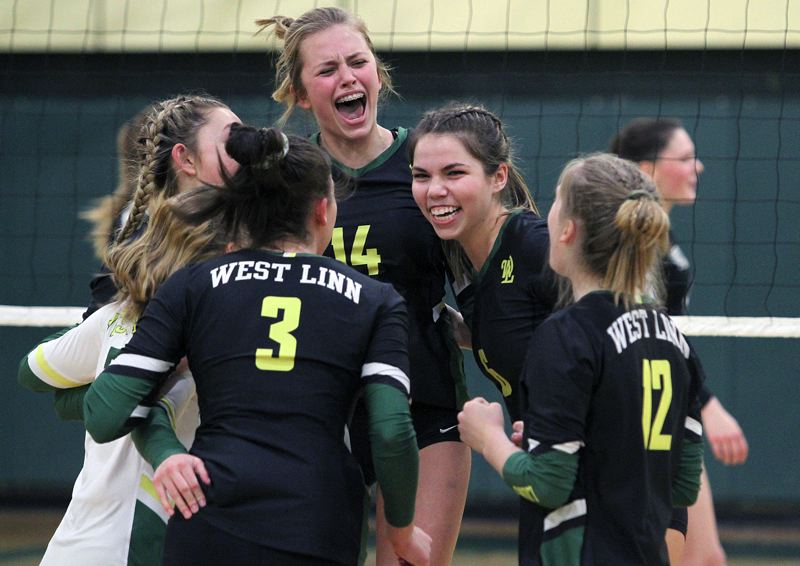 PMG PHOTO: MILES VANCE - The West Linn volleyball team — with Rayna Reynolds (No. 14) and Claire Matthiessen in the middle — celebrate their three-set sweep of Wilson in the second round of the Class 6A state playoffs at West Linn High School on Saturday, Nov. 2.