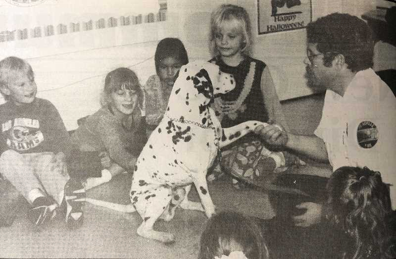 """CENTRAL OREGONIAN - NOVEMBER 3, 1994: Students in Mrs. Ewell's first grade class listen to fire Chief Dave Fields tell what to do in case of a fire. Sparky the Fire Dog demonstrated """"Stop, Drop & Roll."""""""