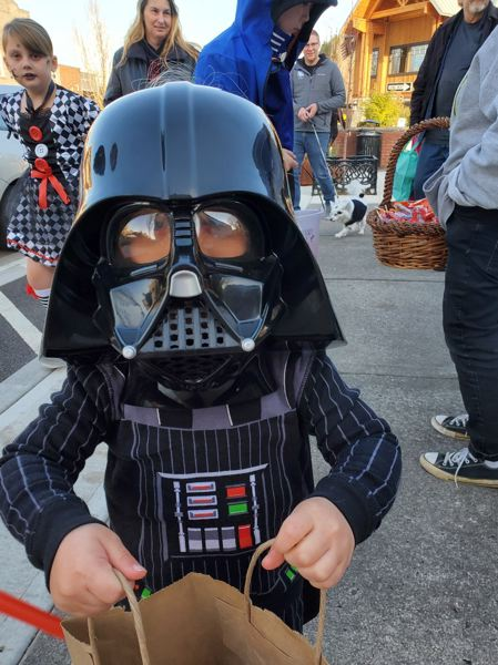 COURTESY PHOTO: DIANE CASTILLO-WHITE - A diminutive Darth Vader scared up a bagful of treats in downtown Troutdale early Halloween evening.