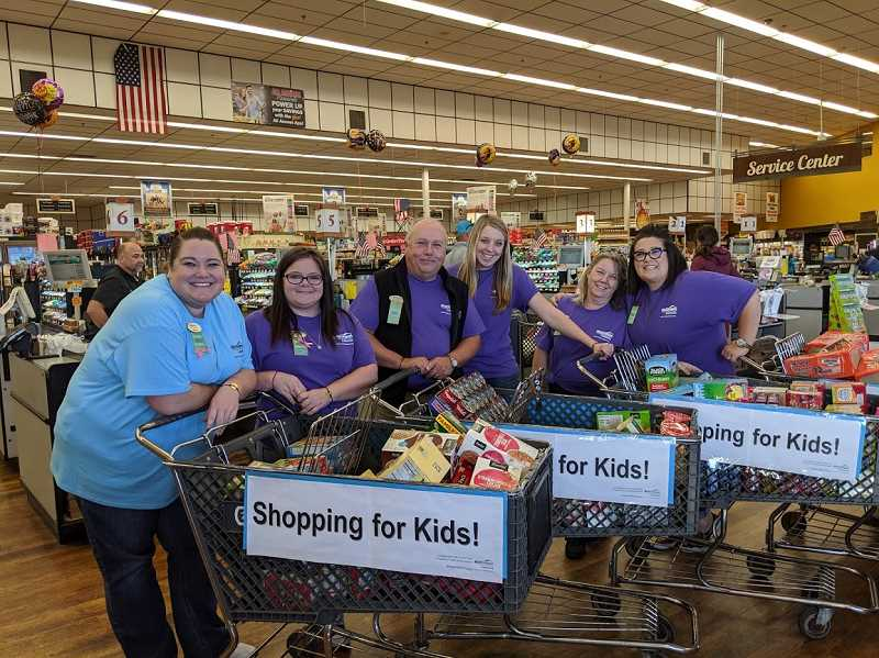 PHOTO CONTRIBUTED BY CROOK COUNTY SCHOOL DISTRICT. - Staff from the Prineville Branch of Mid Oregon Credit Union pause for a photo during their shopping trip at Rays Food Place. The food went towards the Food For Kids Backpack Program for Crook County Schools, and with funds donated from the community, their branch and Rays Food Place, their staff were able to spend $875 on 350 items—such as fruit snacks, granola bars, cereal, and macaroni and cheese.