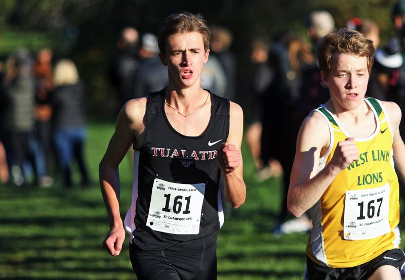 PMG PHOTO: DAN BROOD - Tualatin High School sophomore Samuel Roach (left) finished strong to take second place in the varsity boys race at the Three Rivers League district cross country meet.