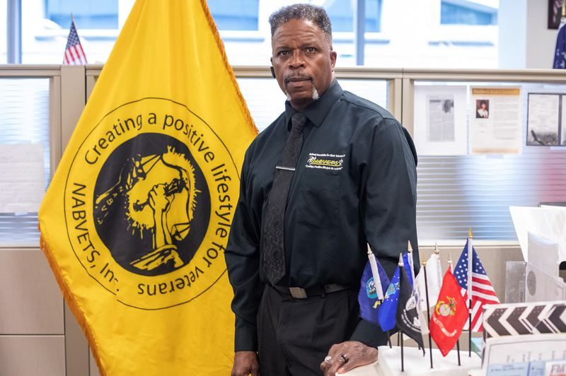 PMG PHOTO: JONATHAN HOUSE - Napoleon Hodgers, Outreach Director of the Portland chapter of the National Association for Black Veterans, stands beside the organization's flag in in his downtown office.