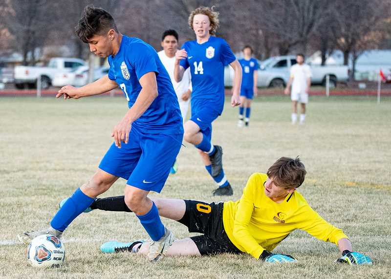 LON AUSTIN/CENTRAL OREGONIAN - Crook County's Kevin Arroyo plays the ball away from Redmond goalkeeper Colin Pearson. Arroyo eventually scored on the play for one of his five goals in the Cowboys' 6-5 win over the Panthers Thursday afternoon in Prineville.