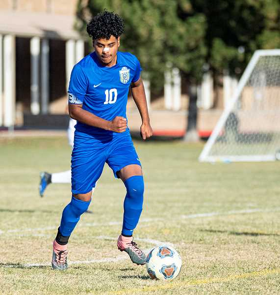 LON AUSTIN/CENTRAL OREGONIAN - Elias Villagomez plays a ball during the Cowboys' 6-5 win over the Redmond Panthers on Thursday. Villagomez, who is one of three seniors on the Cowboy roster, had three assists in the match.