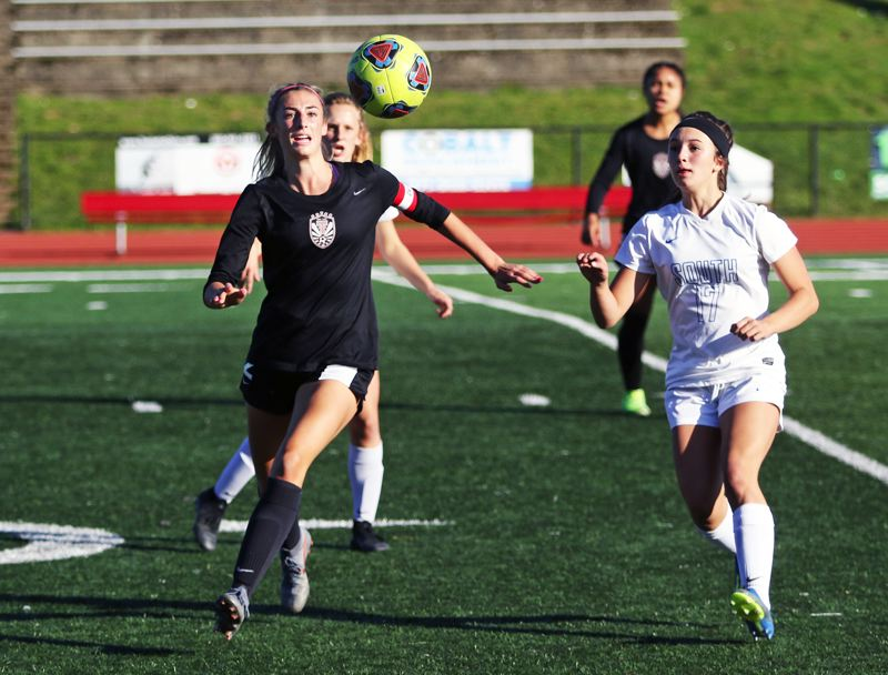 PMG PHOTO: DAN BROOD - Tualatin High School senior Abby Borg (left) races South Medford senior Talia Hutchins to the ball during Saturday's Class 6A state playoff match.
