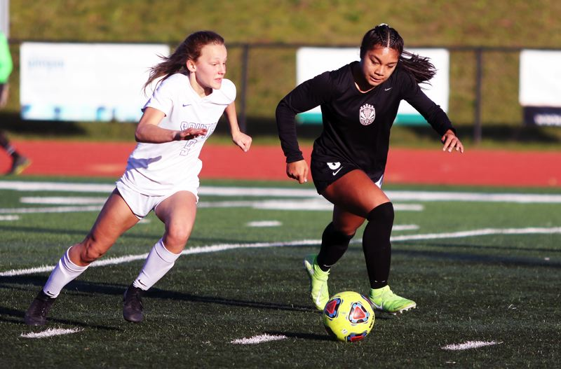 PMG PHOTO: DAN BROOD - Tualatin High School junior Cally Togiai (right) pushes the ball up field ahead of South Medford junior Rainie Dabbs during Saturday's state playoff match.