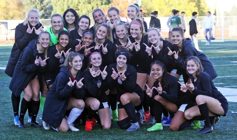 PMG PHOTO: DAN BROOD - The Tualatin High School girls soccer team is all smiles following the 1-0 win over South Medford in Saturday's Class 6A state playoff first-round match.