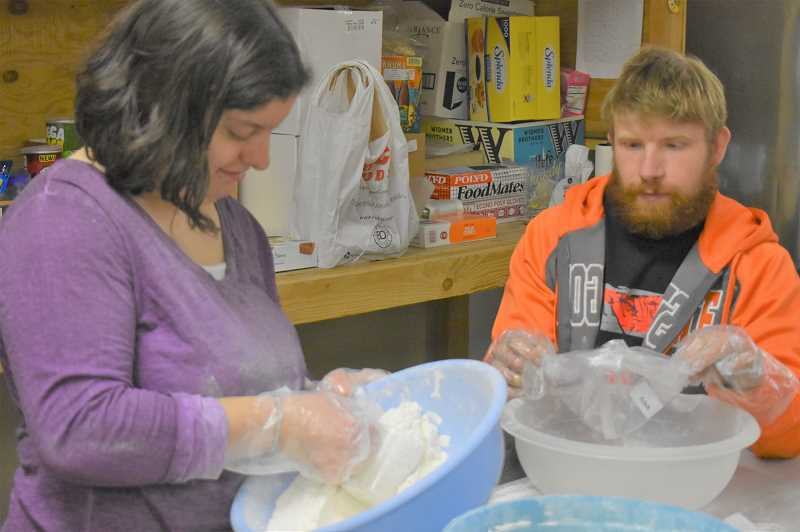 PMG PHOTO: EMILY LINDSTRAND - Abby Bates and Max Spiess package flour at the Estacada Area Food Bank.