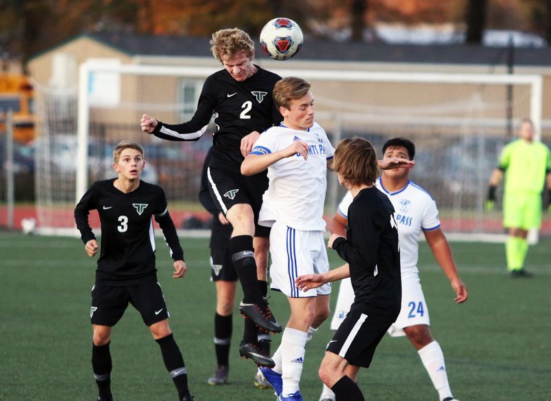 PMG PHOTO: DAN BROOD - Tigard High School sophomore Jack Hallam (2) goes up high to get his head on the ball during the Tigers' 1-0 win over Grants Pass in Saturday's first-round state playoff match.