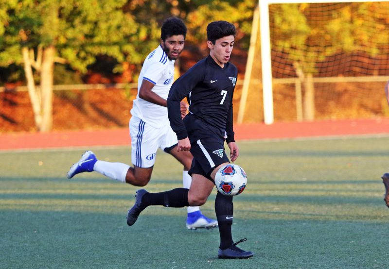 PMG PHOTO: DAN BROOD - Tigard High School senior Rasheed Tarhuni looks to get the ball upfield during the Tigers' 1-0 win over Grants Pass in Saturday's Class 6A state playoff match.