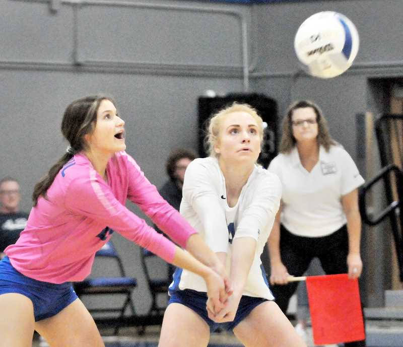 GRAPHIC PHOTO: GARY ALLEN - Seniors Destiny Smith and Isabelle Wyss, among the leaders on the St. Paul volleyball team, go for a ball during their team's resounding victory.
