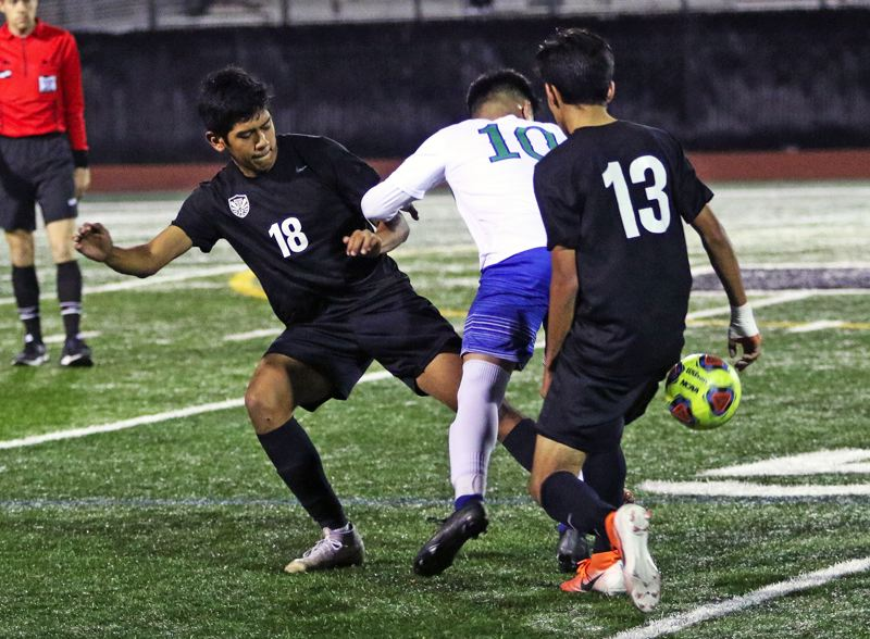 PMG PHOTO: DAN BROOD - Tualatin senior Jose Jacintos (18) and freshman Remus Repcak battle McKay senior Ismael Morales for the ball during Saturday's Class 6A state playoff match. The Wolves won 2-0.