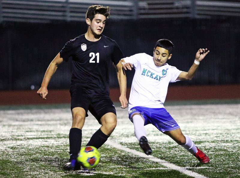 PMG PHOTO: DAN BROOD - Tualatin High School junior Muhammad Faks (left) controls the ball against McKay junor Omar Flores during Saturday's Class 6A state playoff first-round match.