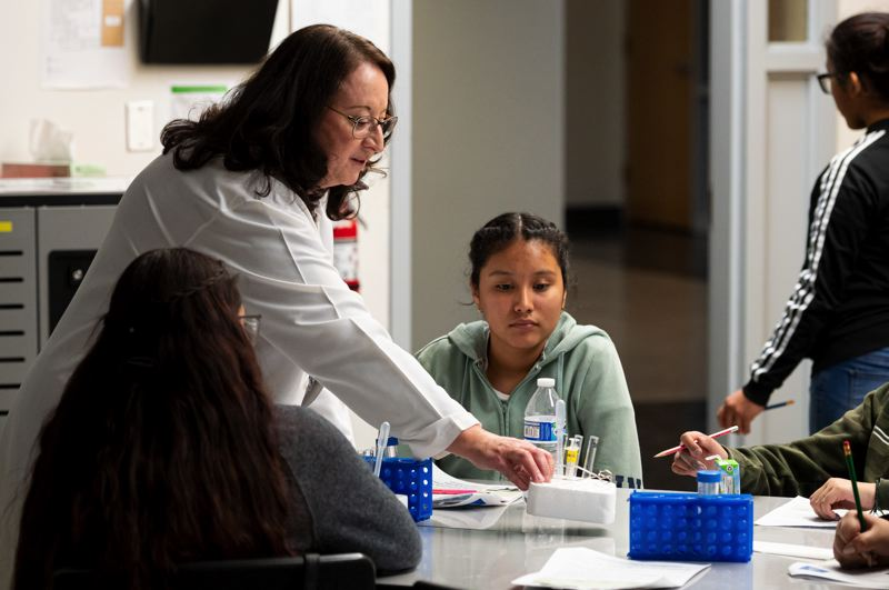 PMG PHOTO: CHRISTOPHER OERTELL - Dr. Mary Zelinski, a researcher at the Oregon National Primate Research Center, shows students in Evergreen Middle School's Girls STEM Career Club how they'll use test tubes during a recent session about cryopreservation.