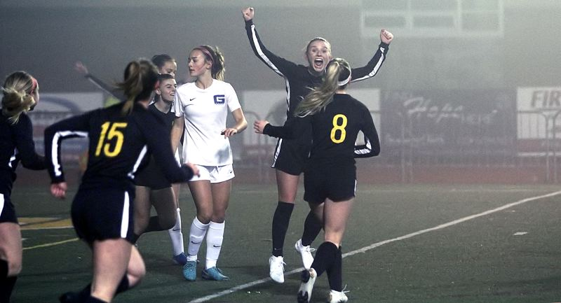 PMG PHOTO: MILES VANCE - West Linn senior Rosie Larsen raises her arms in triumph after scoring the lone goal in her team's 1-0 win over Grant in the second round of the Class 6A state playoffs at West Linn High School on Tuesday, Nov. 5.