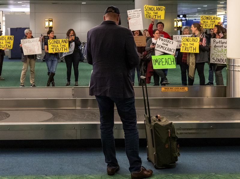 PMG PHOTO: JONATHAN HOUSE - Sondland waited alone at the baggage claim Tuesday night after returning from Washington, D.C., accosted by a mostly polite group of protesters, before airport security personnel escorted him to a back room to get his luggage.