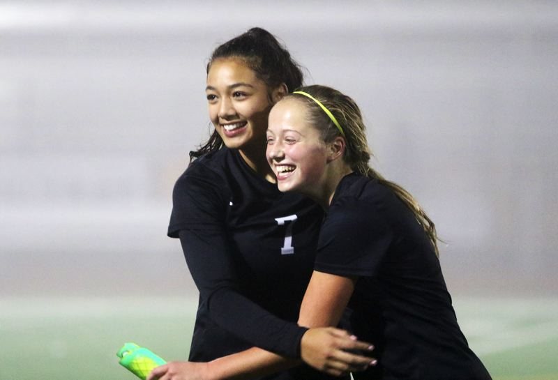 PMG PHOTO: DAN BROOD - Sherwood High School senior Loma McNeese (left) and junior Morgen Fried are all smiles following the Lady Bowmen's 4-2 overtime win over Lake Oswego in Tuesday's state playoff match.