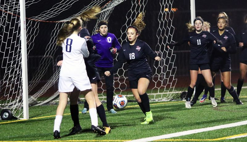 PMG PHOTO: DAN BROOD - Sherwood High School senior defender Isa Frost (18) looks to knock away a Lake Oswego corner kick during the Bowmen's 4-2 state playoff victory on Tuesday.