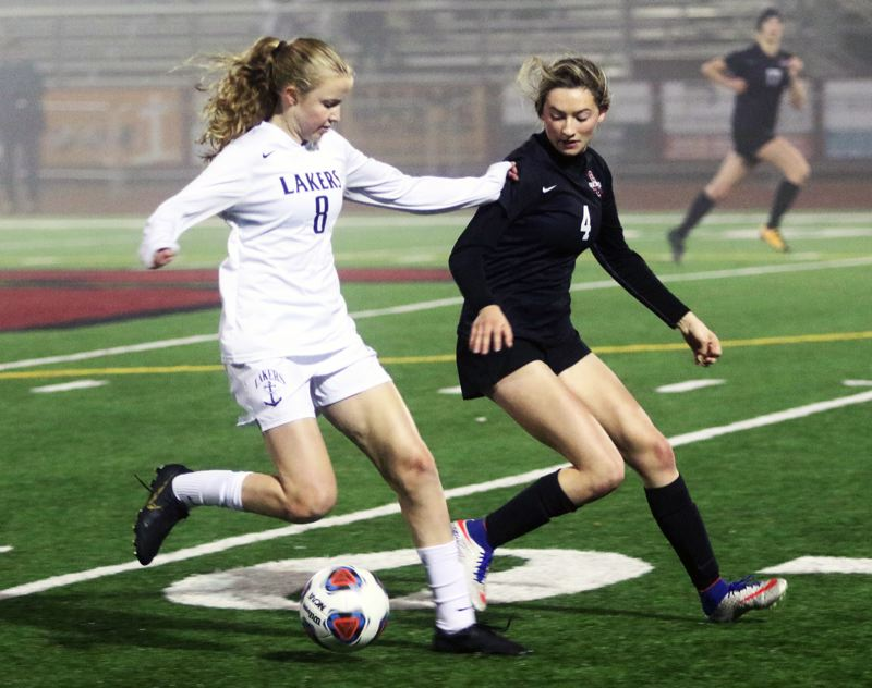 PMG PHOTO: DAN BROOD - Sherwood High School senior Ava Boughey (right) looks to get the ball from Lake Oswego freshman Kaitlyn Sasadeusz during Tuesday's state playoff second round match.