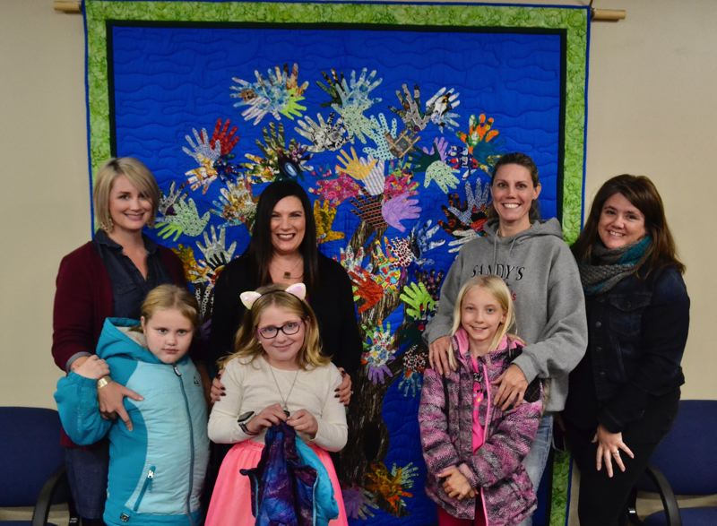 PMG PHOTO: BRITTANY ALLEN - Sandy's Helping Hands founder Machel Heldstab (left, center), with the help of MacKensey Pulliam (left) and other volunteers presented the quilt as a donation for the city and it's neighbors to Sandy City Council on Monday, Nov. 4.