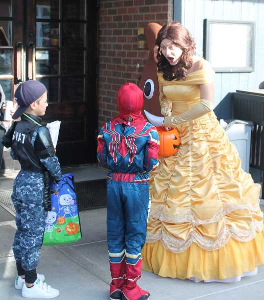 PMG PHOTO: HOLLY BARTHOLOMEW - Belle from Beauty and the Beast is shocked by something Spiderman and a SWAT team member tell her.