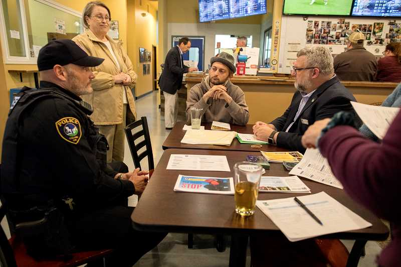 PMG PHOTO: JAIME VALDEZ - Tigard Officer Eric Enzenberger and Mayor Jason Snider listen to Sebastian Salway, a citizen of Tigard, address his concerns Tuesday night during a Council, Cops and Conversation night, hosted by Fidos -- Worlds First Dog Tap House.
