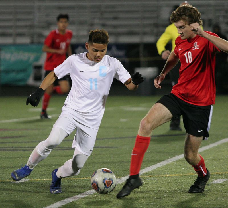 PMG PHOTO: JIM BESEDA - Centennials Aye Doh Chan looks to move past Clackamas Colm Dady in the midfield during the Eagles 1-0 second-round playoff win Wednesday.